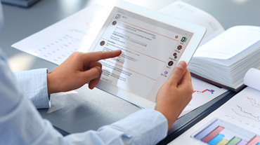 Person at desk holding tablet pointing at screen